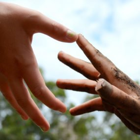 Close up of hands reaching for one another