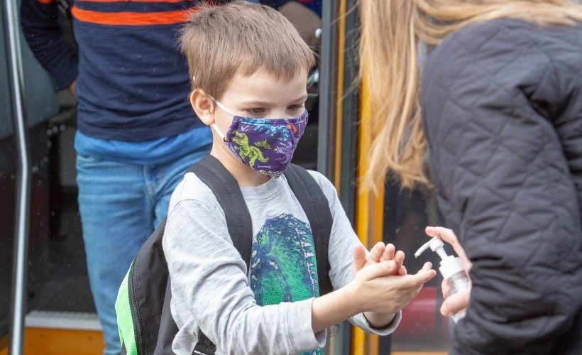 Elementary student getting off bus with mask