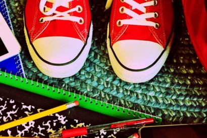Top down view of an assortment of school supplies and red Converse