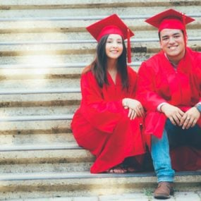 Two Crescent Valley High School 2017 graduates sitting on stairs